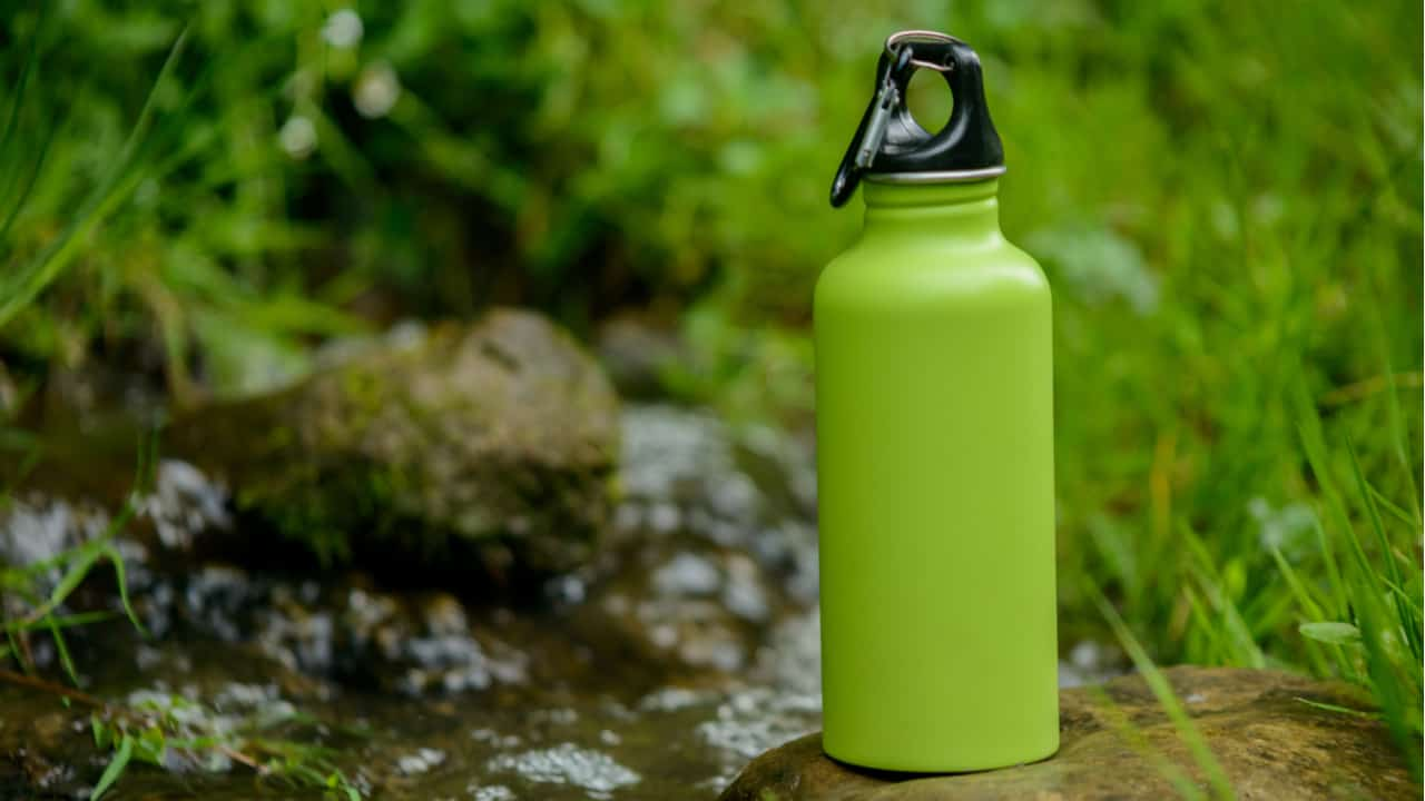 Green Hydro Flask on a stone