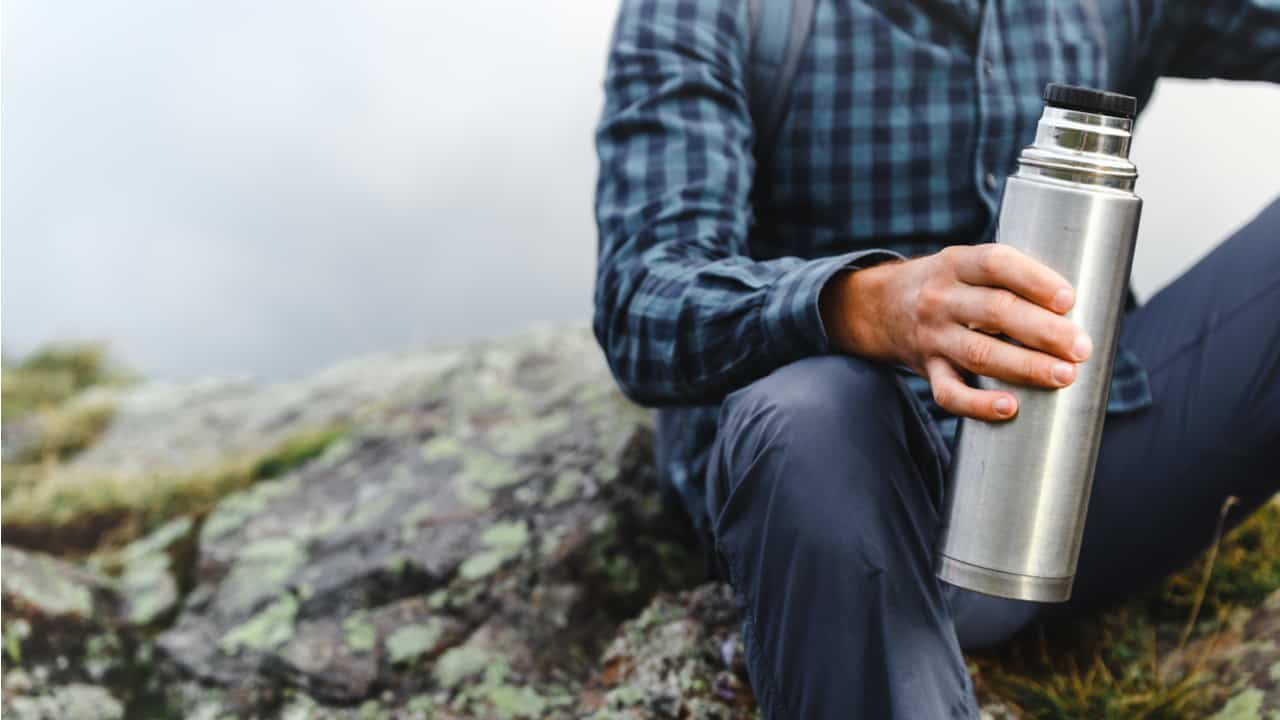 Hiker holding a Thermos bottle