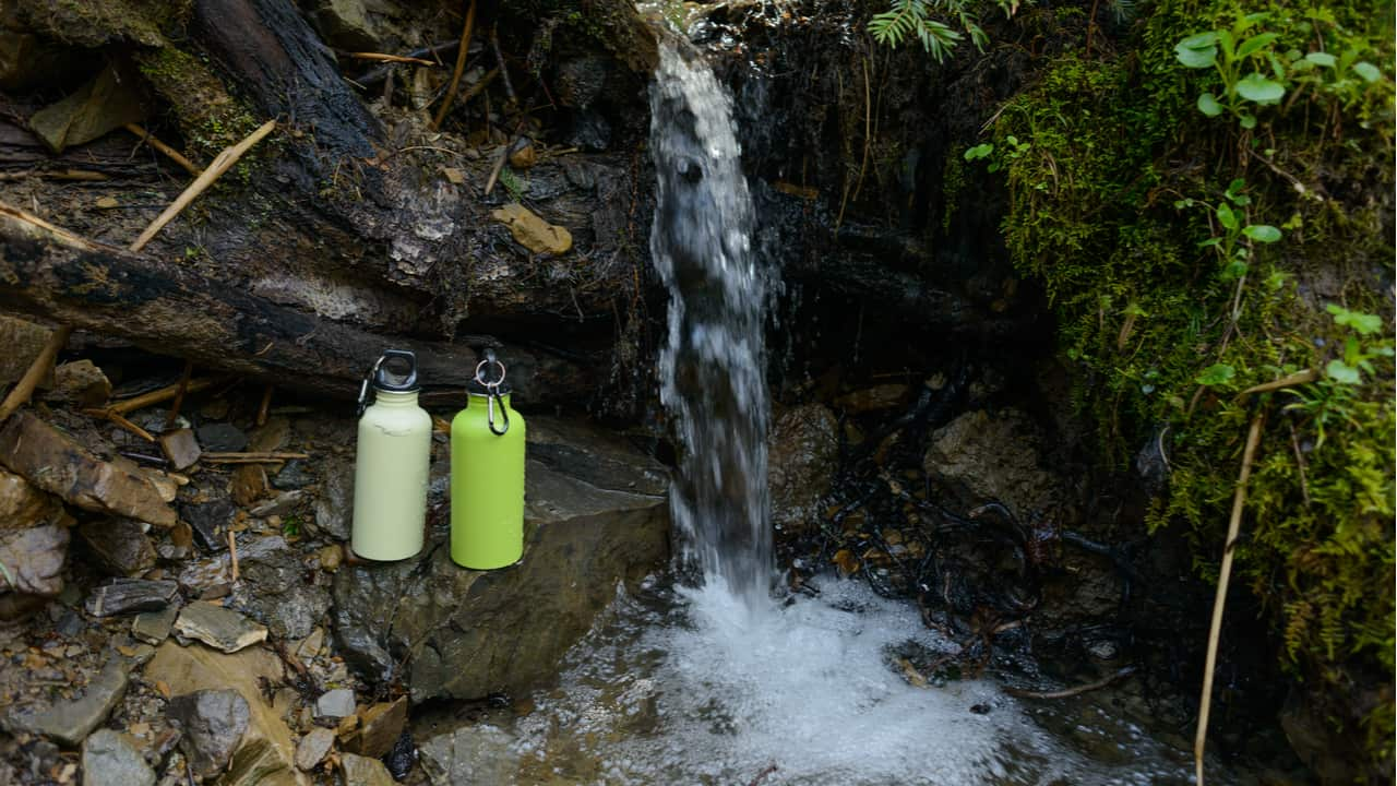 Two Hydro Flask bottles next to a waterfall